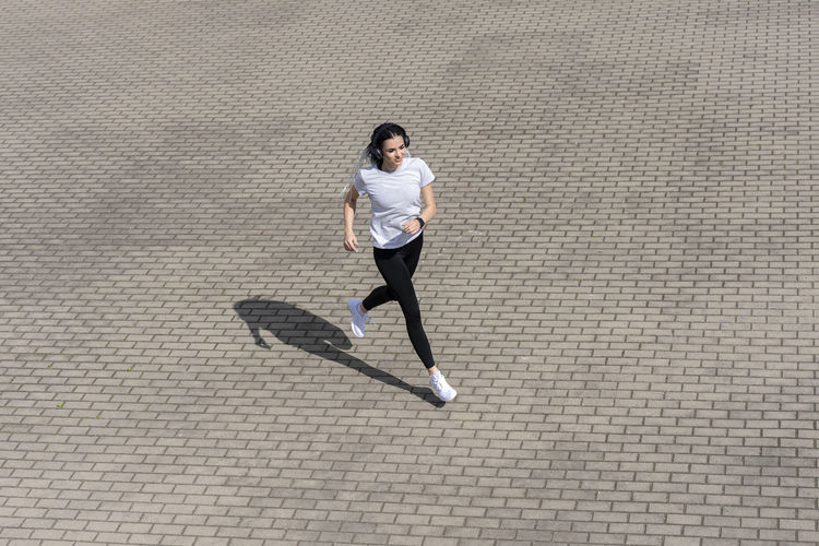 Full length of woman running on sidewalk in city