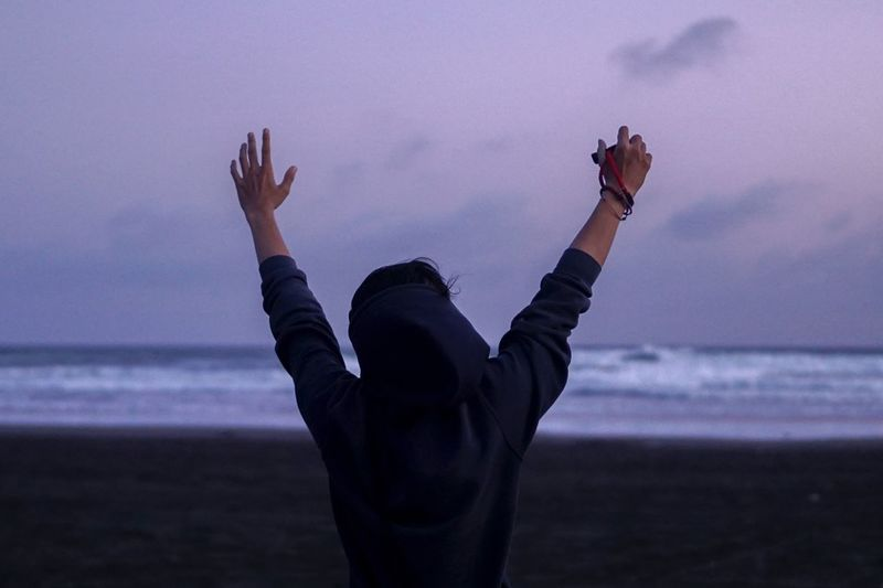 Rear View Of Person With Arms Raised Standing At Parangtritis Beach During Dusk