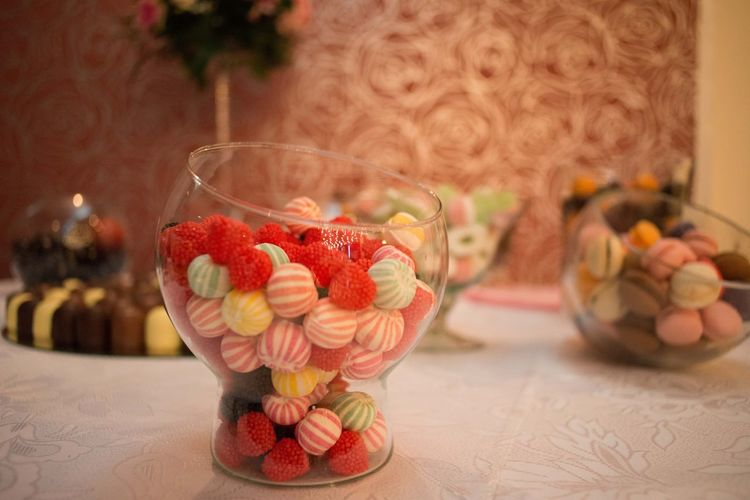 Close-up of candies in glass container on table