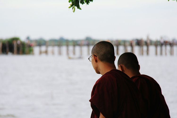 Rear view of monks against sky