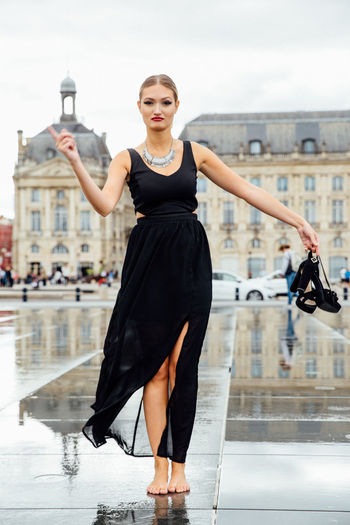Portrait of confident young woman standing on wet street in city