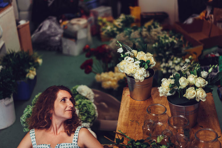 High Angle View Of Woman Looking At Flowers In Container On Table At Flower Shop
