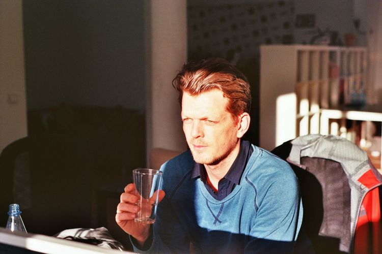 Young thoughtful man drinking water