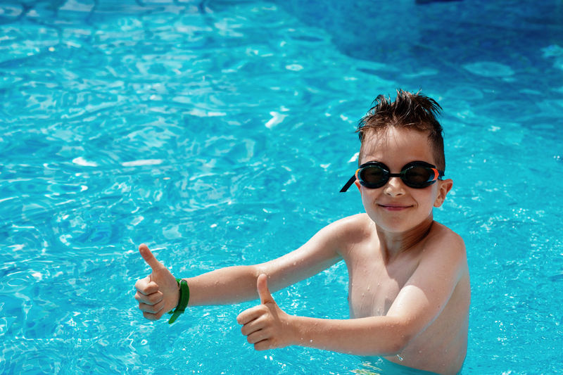 Portrait of smiling boy showing thumbs up wearing swimming goggles in pool
