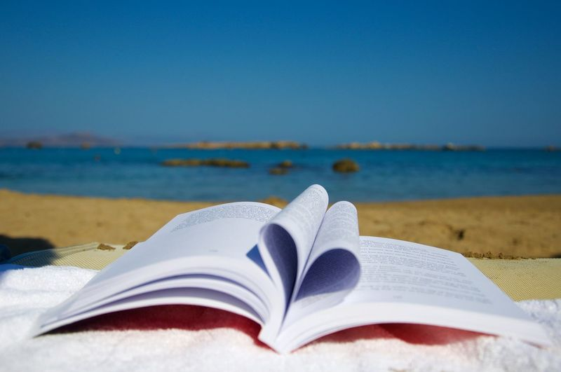 Close-up of open book on beach against blue sky