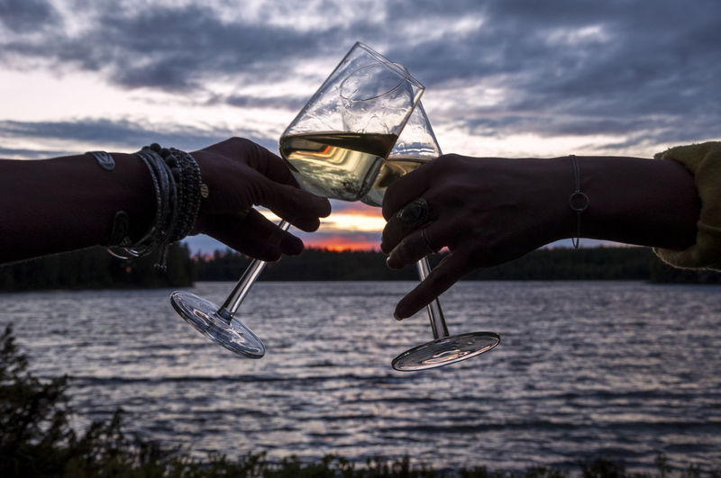 Cropped Image Of Couple Toasting Wineglass By River During Sunset