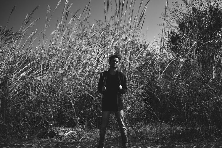 Portrait of young man standing on land against plants
