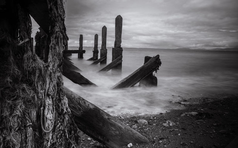 Abandoned Wooden Structure At Beach Against Cloudy Sky