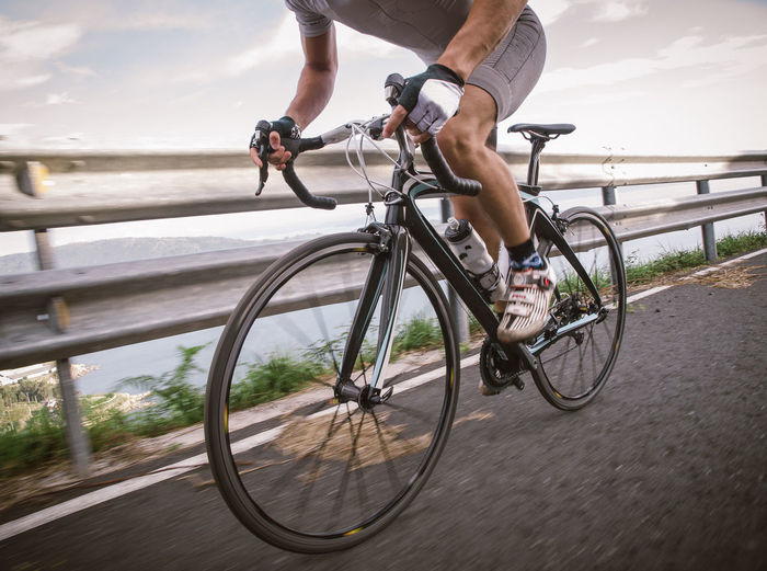 Low section of man riding bicycle on road against sky