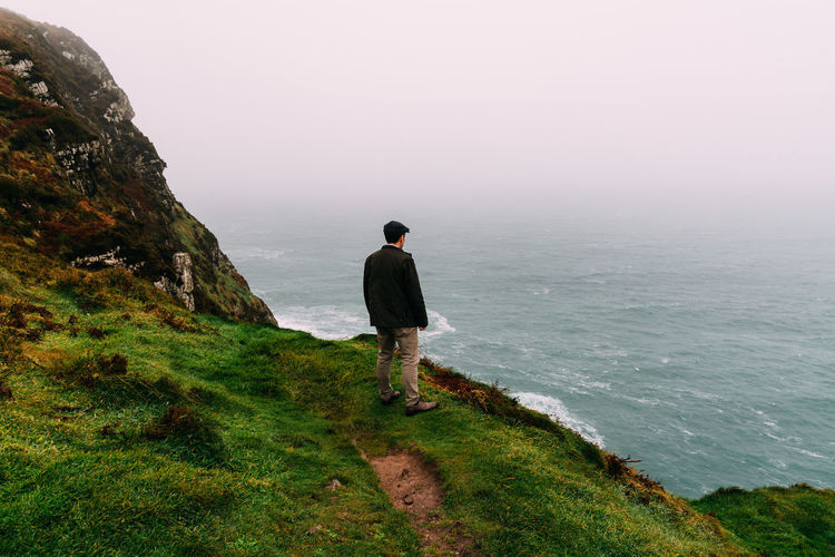 Man wearing cap at Brandon Point Cliffs in Ireland Brandon Point Irish Misty Misty Morning Fog Peaky Blinders Cap Cliff Ocean Wild Atlantic Way Water One Person Sea Beauty In Nature Real People Scenics - Nature Full Length Rear View Sky Grass Tranquil Scene Tranquility Nature Leisure Activity Standing Land Non-urban Scene Lifestyles Idyllic Looking At View Outdoors