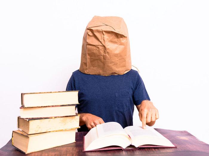 Full length of man reading book on white background