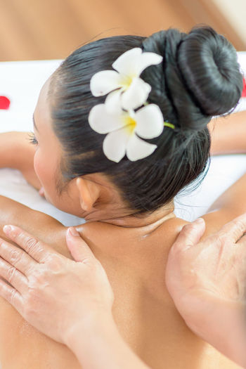 Cropped hands of therapist massaging woman back at health spa