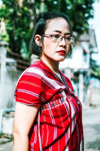 Portrait of beautiful woman standing against red shirt.