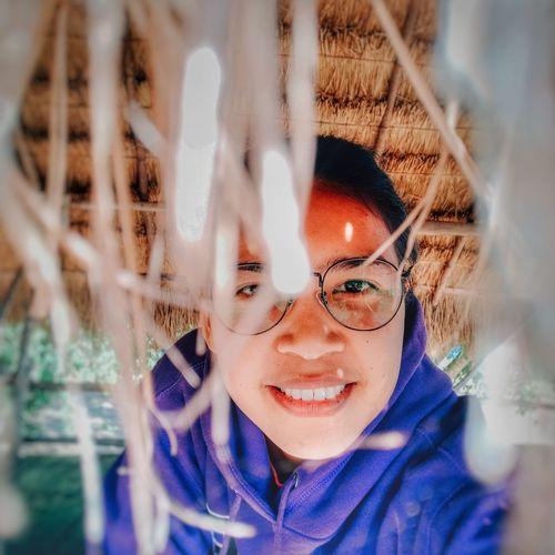Portrait of smiling woman wearing eyeglasses in hut