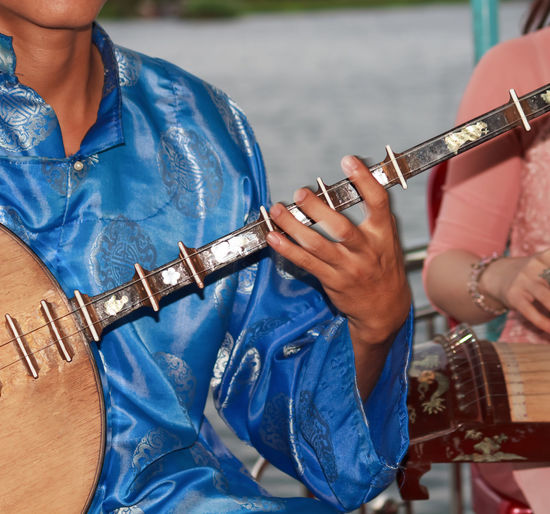 Midsection of man playing string instrument