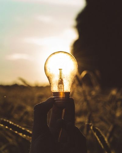 Focus On Foreground Close-up Sunset Light Bulb Sky Illuminated Outdoors Burning Electricity  Flame Human Hand Technology One Person Day People