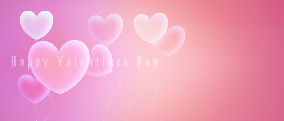 Close-up of heart shape with pink balloons against wall