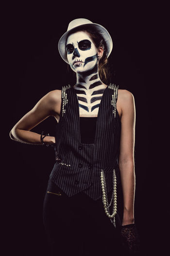 Woman with skeleton face art Black Background Day Of The Dead Halloween Hat Horror Looking At Camera Make-up Makeup Skeleton Woman Body Arts Concept Conceptual Face Art One Person People Skull Studio Shot Young Adult