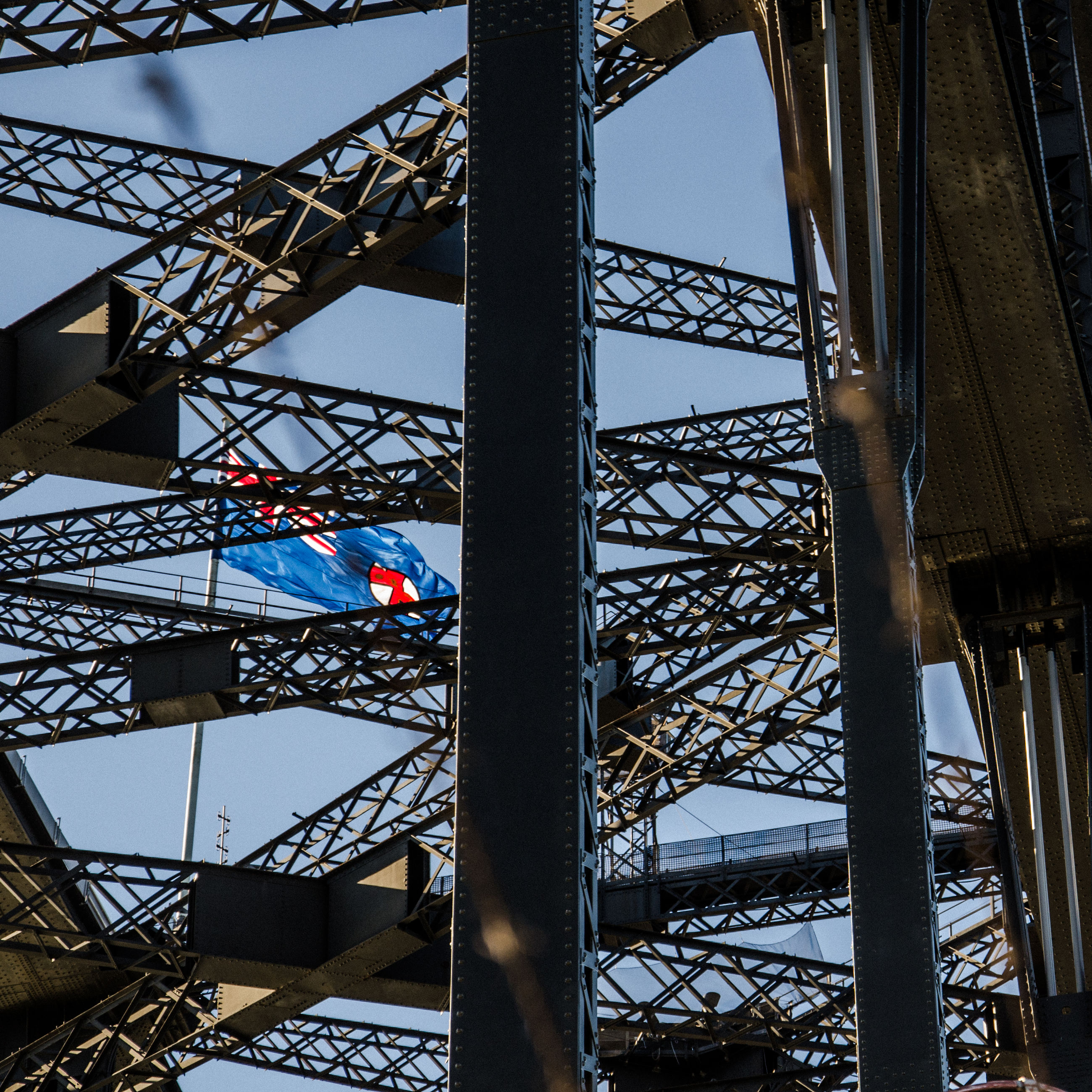 architecture, built structure, metal, low angle view, day, outdoors, nature, no people, sky, arts culture and entertainment, connection, bridge, bridge - man made structure, blue, flag, travel destinations, city, grid