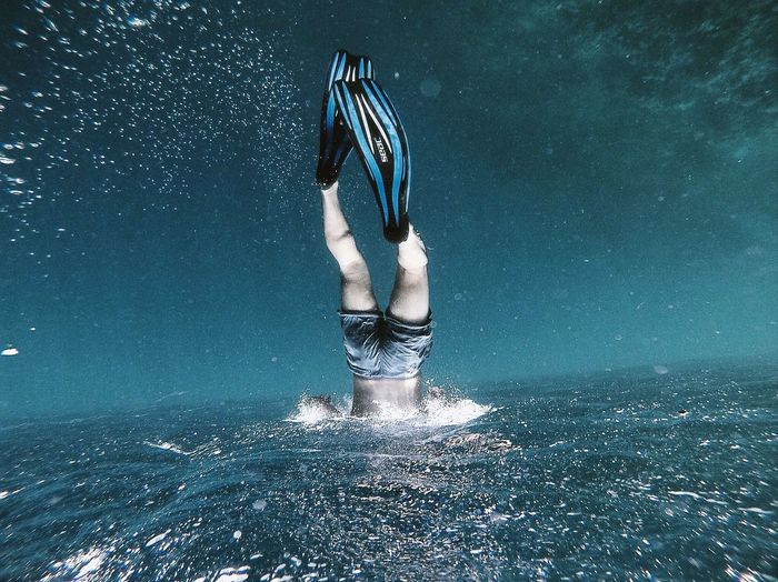 Low section of man swimming in sea