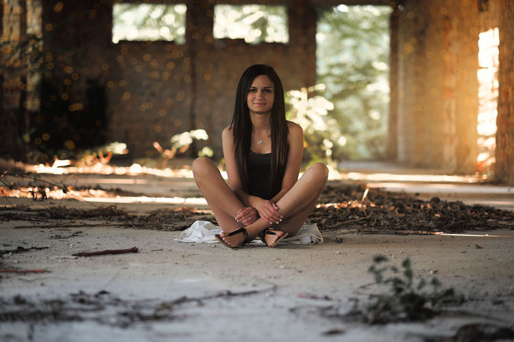 Portrait of young woman sitting in abandoned building