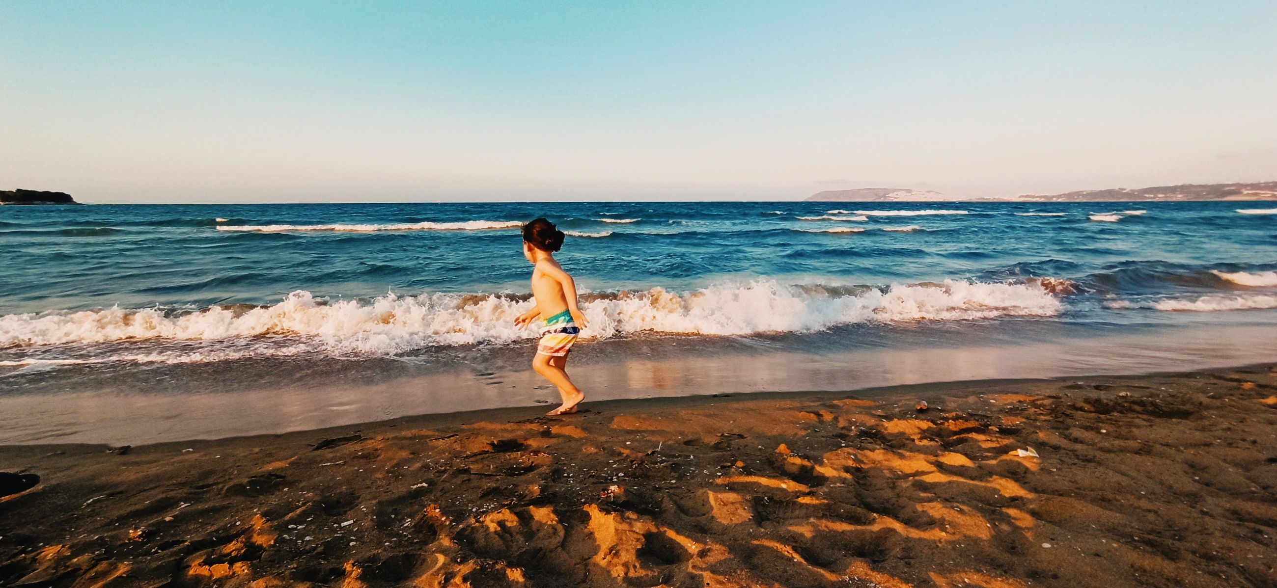 sea, water, land, beach, sky, ocean, body of water, shore, one person, wave, motion, horizon, horizon over water, full length, sand, nature, beauty in nature, coast, leisure activity, holiday, vacation, trip, sports, sunset, scenics - nature, lifestyles, adult, standing, wind wave, clear sky, tranquility, women, clothing, idyllic, person, day, outdoors, rear view, surfing, young adult, sunlight, child, water sports, travel destinations, tranquil scene, childhood, summer, enjoyment, rock, travel, relaxation