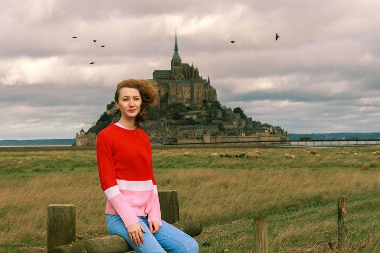 Portrait of young woman on land against the mont-saint-michel