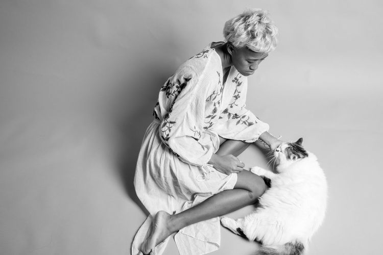 High angle view of woman with cat sitting against white background