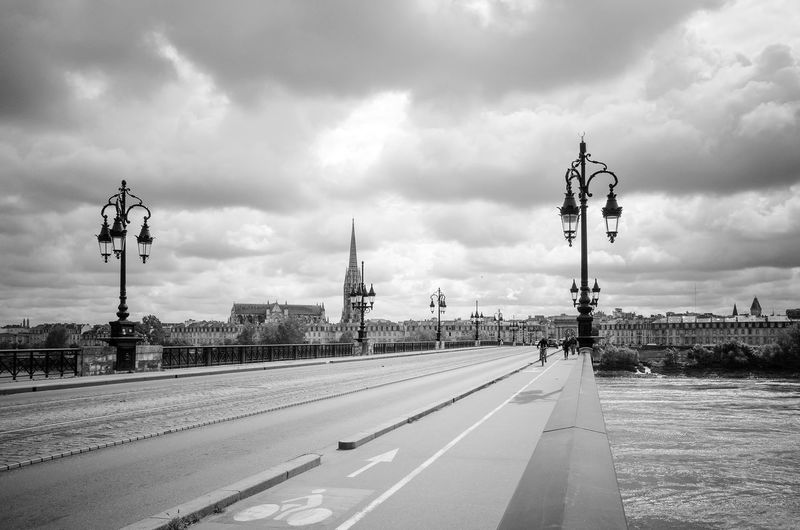 Bridge over river by church against cloudy sky in city