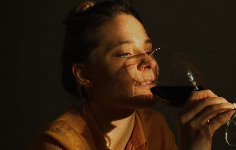 Close-up of woman drinking wine against wall