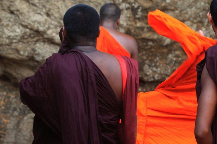 Rear view of monks praying in front of sigiriya rock