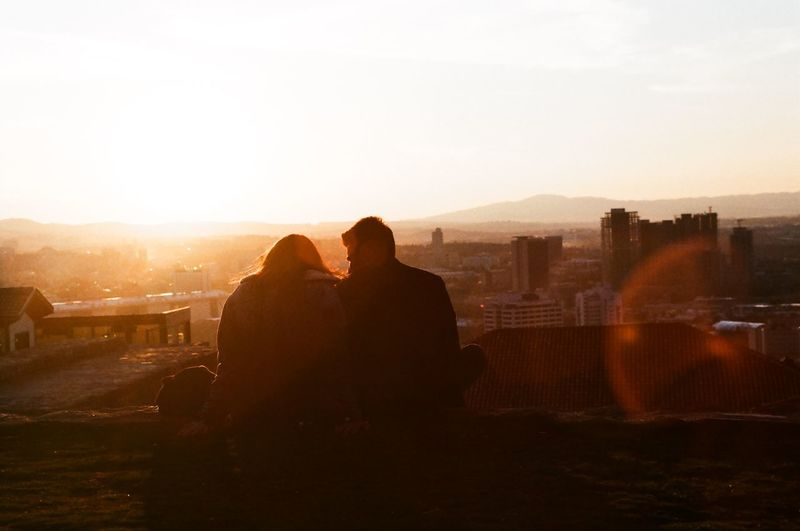 Rear view of man looking at cityscape against sky during sunset