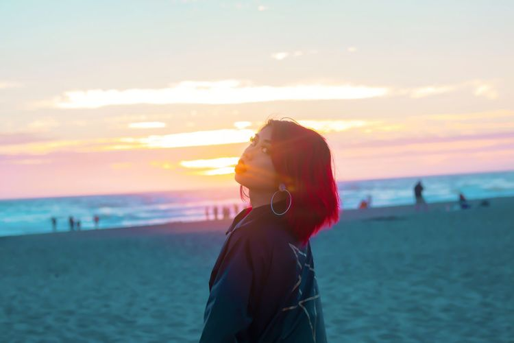 Portrait Of Young Woman With Dyed Hair Standing At Beach Against Sky During Sunset