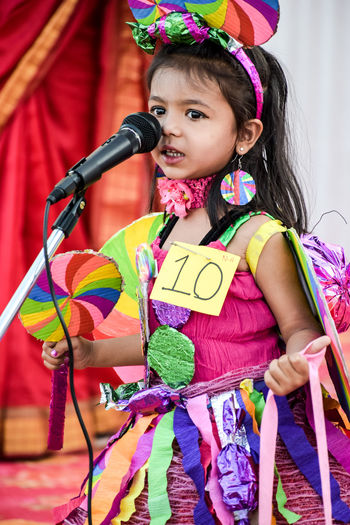 Cute girl wearing costume standing by microphone