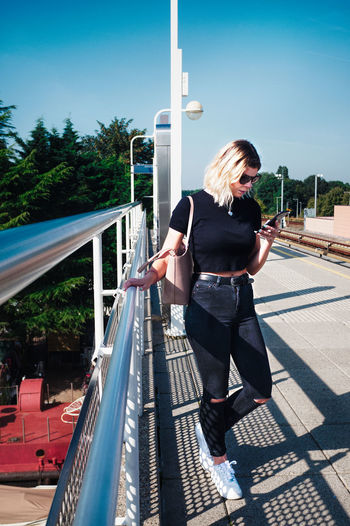 Woman standing on railing against sky on sunny day