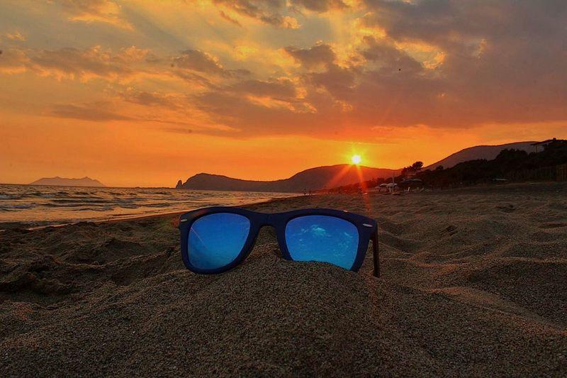 Sunglasses on sandy beach at sunset
