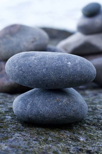 Close-up of stone stack on rock at beach