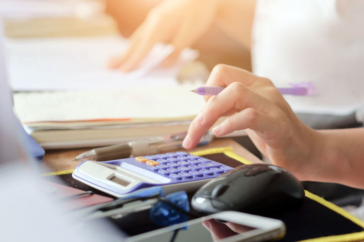 Close-Up Of Businesswoman Using Calculator At Desk