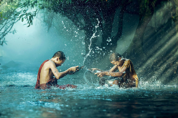 Monks splashing water in river