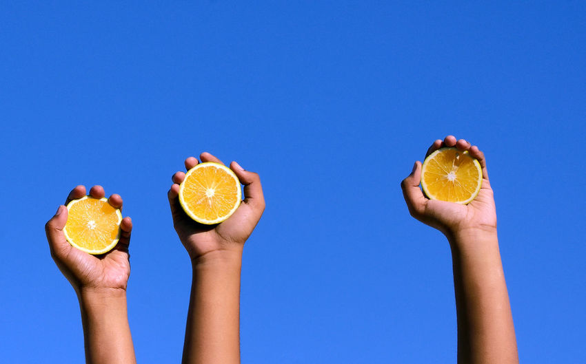 EyeEm Selects Yellow on Blue , it strikes so true. Human Hand SLICE Holding Day Clear Sky Healthy Eating Freshness Fruit Fruit Photography Citrus  Citrus Fruit Juicy Fruit Juicy Food Colors Outdoors Sky Lemon SLICE Conceptual Image Abstract Low Angle View