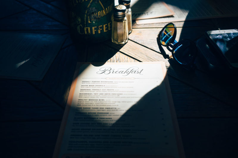 Breakfast Menu Architecture Book Cafe Menu Communication Day Education High Angle View Indoors  Menu Music No People Open Paper Publication Shadow Still Life Table Text Typo Western Script