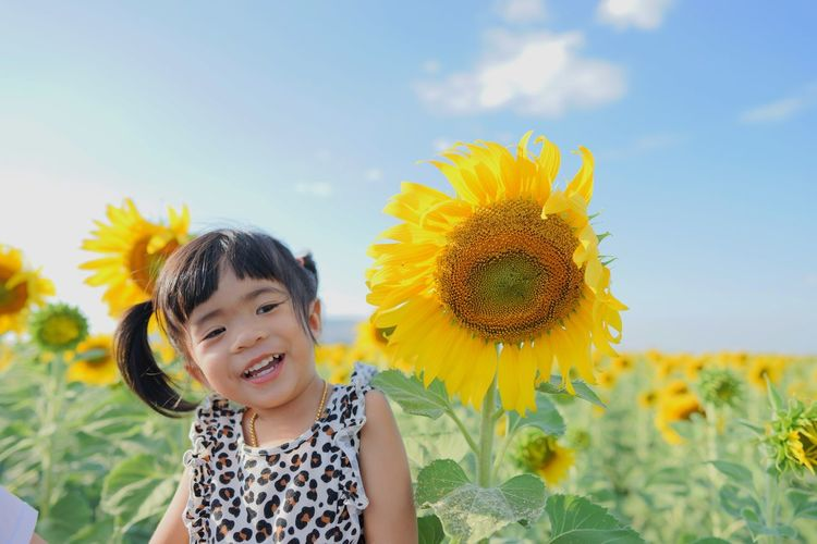 Smiling girl standing by sunflowers