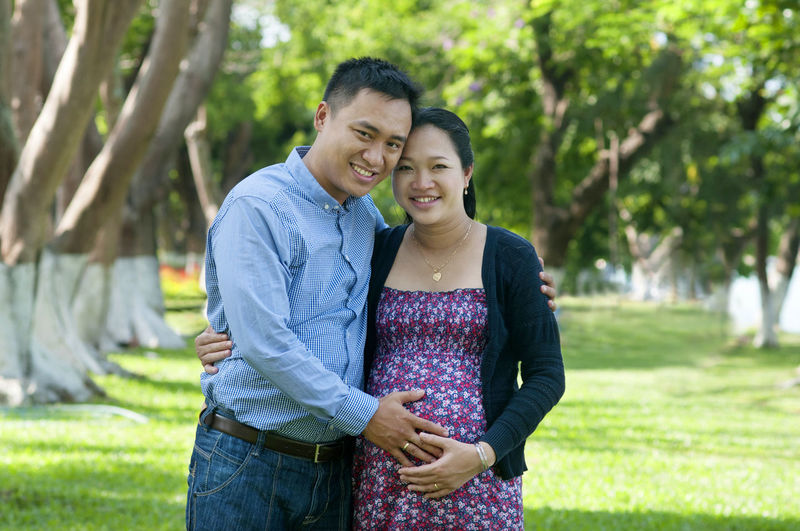 Portrait Of Man With Pregnant Wife Standing On Field