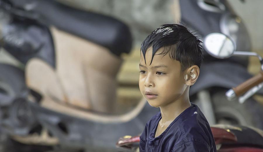 Boy looking away against motor scooters