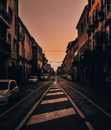 Road by buildings in city against sky during sunset