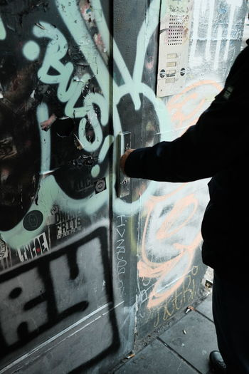 Close-up of person standing by graffiti on city