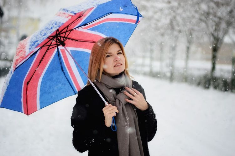 Portrait of woman with umbrella standing in snow