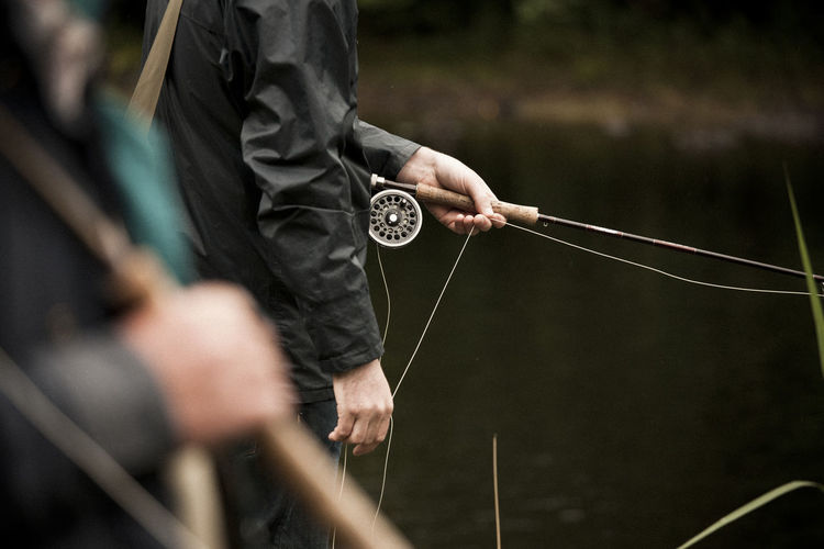 Midsection of man holding fly fishing rod