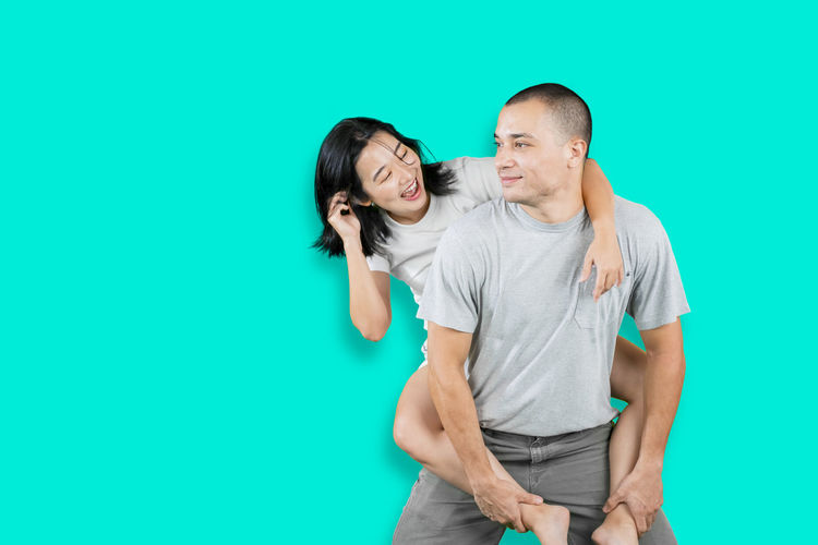Young couple standing against blue background