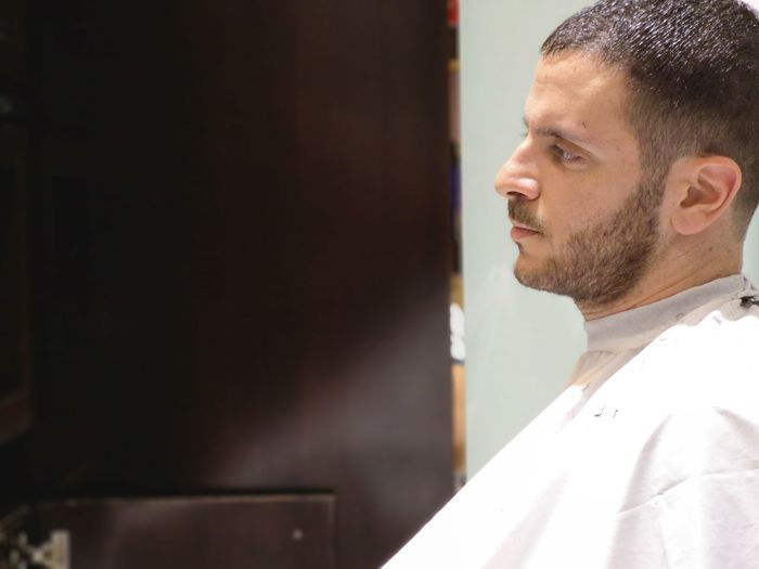 Side View Of Man Wearing Cape Looking Away While Sitting In Hair Salon